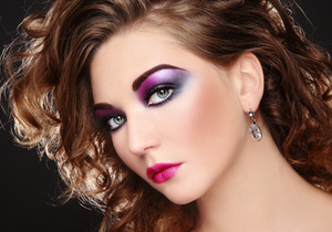 Beautiful young girl with glowing colorful disco make-up and curly hairstyle